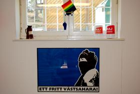 Prideflagga, insamlingsbössor och bild med texten Ett fritt Västsahara.