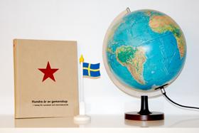 Boken Hundra år av gemenskap, svensk flagga och jordglob.