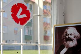 Liten V-flagga och bild av Karl Marx.