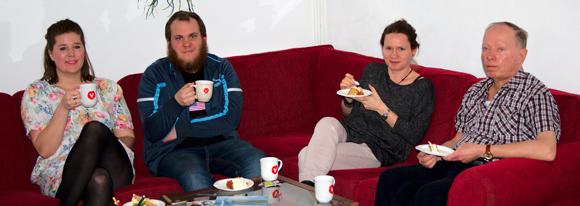Tove, Rickard, Annika och Erik med kaffe och tårta i vår röda soffa.