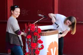 Annika och Tove dekorerar talarstolen med V:s partisymbol.