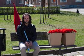 Deltagare med röd flagga och nejlikor på en bänk.