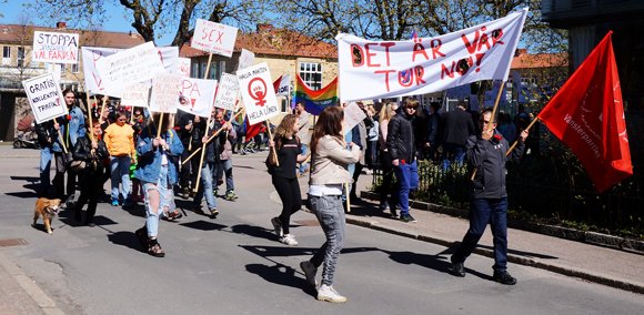 Isabell och Carlos med Det är vår tur nu-banderoll samt andra deltagare med plakat.